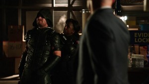 Liza holds Oliver at knifepoint in front of Captain Lance. Arrow Beyond Redemption
