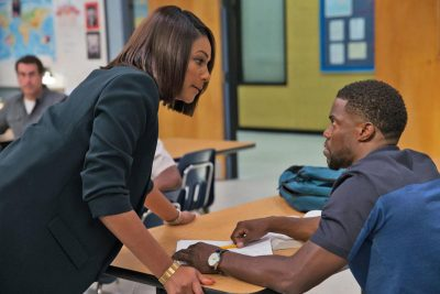 Carrie (Tiffany Haddish) leans over desk to confront Teddy Walker (Kevin Hart)
