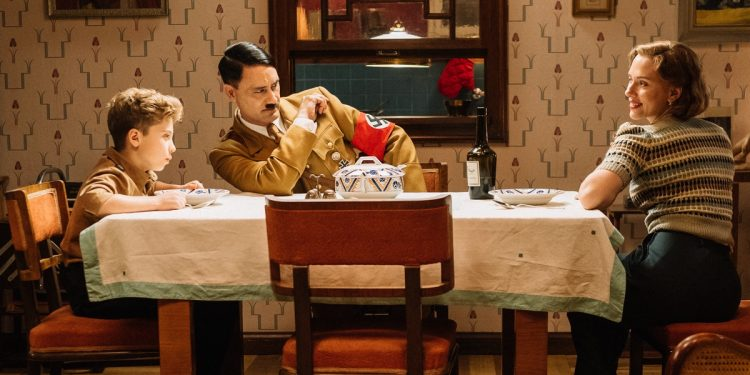 Jojo Rabbit: Jojo (Roman Griffin Davis) has dinner with his imaginary friend Adolf (Writer/Director Taika Waititi), and his mother, Rosie (Scarlet Johansson