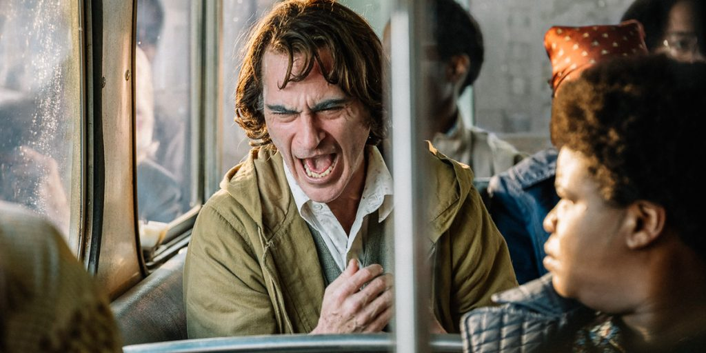 Joker:  Joaquin Phoenix as Arthur laughs uncomfortably on bus