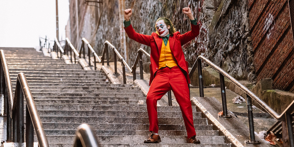 Joker: Arthur dressed as a clown dancing on stairs