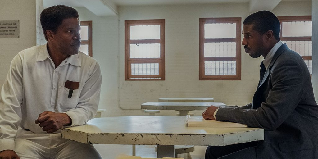 Jamie Foxx (Walter McMillian) and Michael B Jordan (Bryan Stevenson) look at each other across a table in a prison waiting room