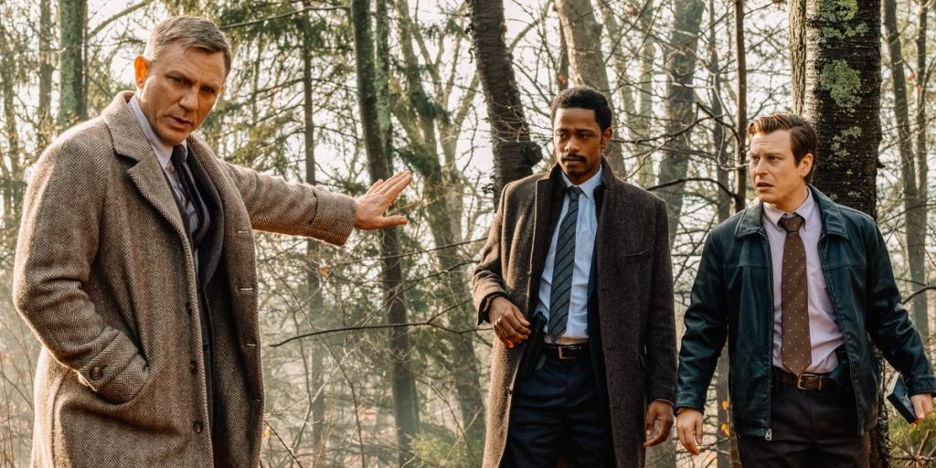 Daniel Craig (Benoit Blanc) holds hand out to tell LaKeith Stanfield (Lt Elliott) and Noah Segan (Trooper Wagner) to stop