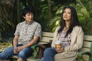 KE LUY QUAN as GEORGE, KELLY HU as LEILANI in FINDING 'OHANA. George and Lellani sit on a bench. George looks over at Leilani who appears distressed.