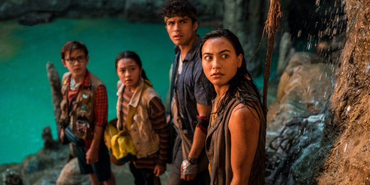 (L to R) OWEN VACCARO as CASPER, KEA PEAHU as PILI, ALEX AIONO as E, LINDSAY WATSON as HANA in FINDING 'OHANA. All four characters are wet and standing at the edge of a cave pool looking up increduously