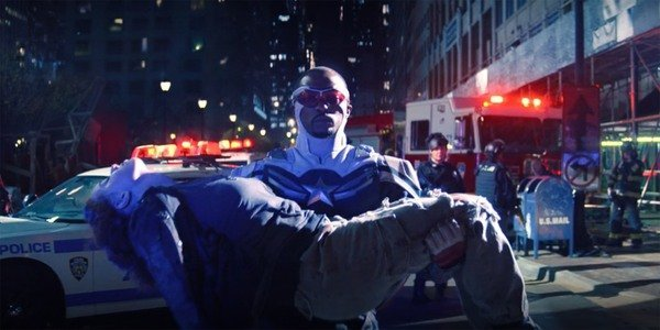 Still from the finale of The Falcon and the Winter Soldier. Sam dressed in his Captain America uniform holds the dead body of Karli Morgenthau in his arms.
